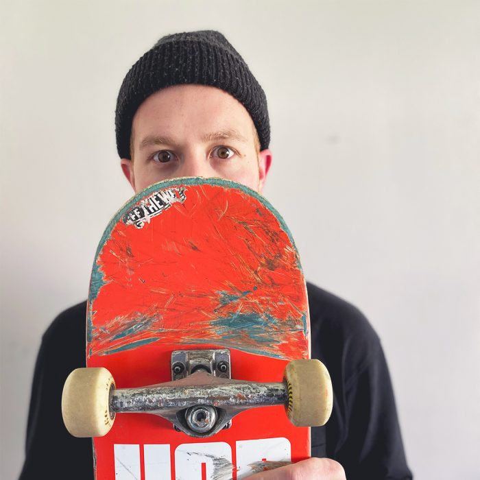 Michael Nolan with skateboard covering face